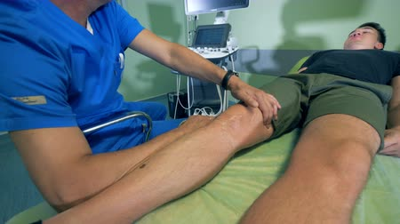sonography : Mans leg is getting scanned during an arthroscopy