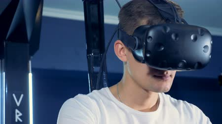 interaktivní : A young man is wearing virtual reality headset and playing 360 virtual reality game.