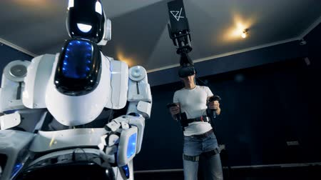 irreal : Young man is putting on virtual glasses and starts to navigate a robot with VR equipment
