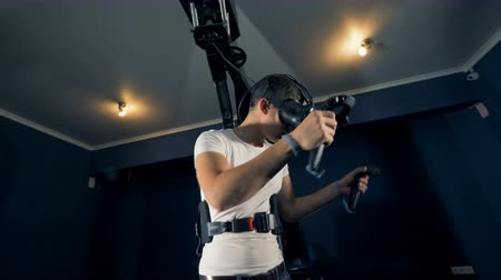 interativo : Virtual reality gaming concept. Young man in the middle of gaming process with a virtual reality system