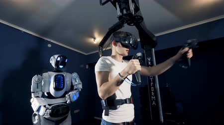 bot : A young man and a cyborg are moving their hands and bodies in synch through virtual reality