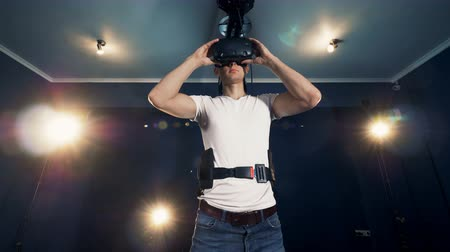 imaginário : A guy putting on VR goggles and starts moving his hands. Virtual reality headset playing game 360.