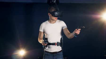 imaginário : Young man is using a virtual reality device and moving hands. Virtual reality headset playing game 360. Stock Footage