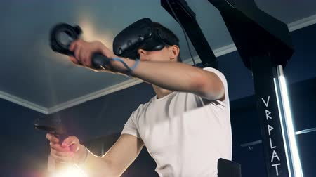 imaginário : Virtual reality headset playing game 360. Virtual reality system is being used by a man whos moving his hands