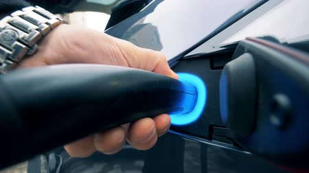 economical : Man charges an electric vehicle. A person holds a charger, standing near an electric car. Stock Footage