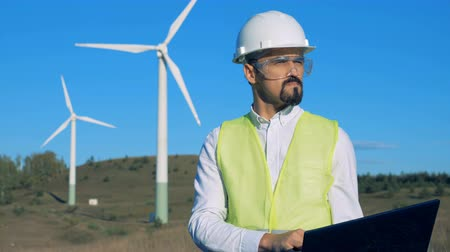 energetyka : An engineer is operating a laptop in front of windmills. Clean, eco-friendly energy concept.