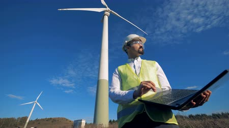 navigating : Wind turbines are revolving while a technician is operating a laptop. Clean, eco-friendly energy concept.