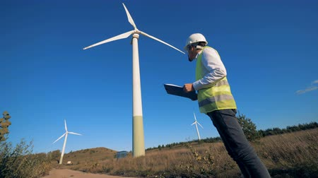 energetyka : Male technician with a clipboard is observing several windmills. Clean, eco-friendly energy concept.