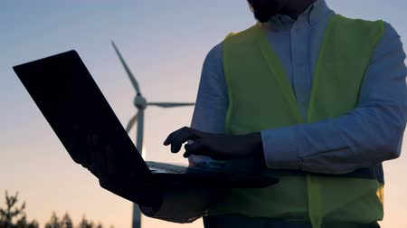 energetyka : Close up of a laptop in the hands of a male worker standing near a turbine tower. Clean, eco-friendly energy concept. Wideo