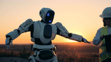 avançar : Engineer is manipulating a robot by his laptop in sunset landscape