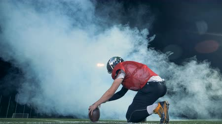 holding steady : Stadium filled with smoke and a ball getting kicked out from it by American football player