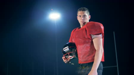 halfback : Male American football player player is standing with his helmet at the stadium at night Stock Footage