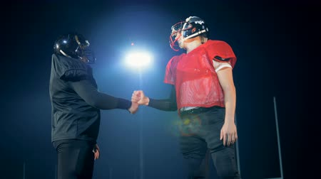 american football player : Playful handshake of two sportsmen on a football field