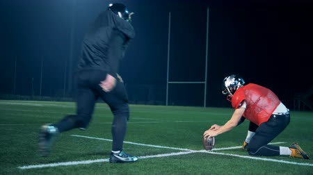 хит : American football ball is getting kicked out from between the ground and players hand