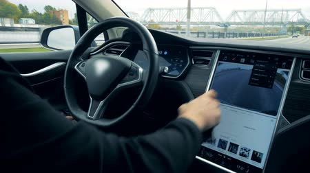 charged : Driver types on a monitor while a car going on autopilot, close up. Stock Footage