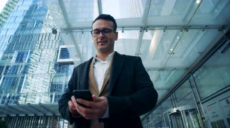 red centre : Attractive businessman with a smartphone is standing near business skyscrapers. Stock Footage