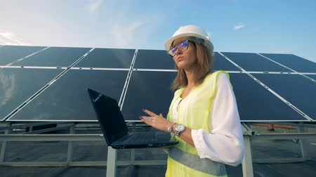 energetyka : Solar energy specialist is walking along a battery construction with her laptop Wideo