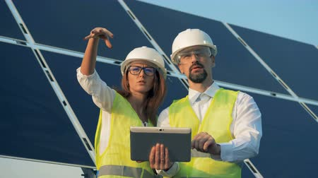 energetyka : Two technicians are discussing construction project with a solar installation behind them