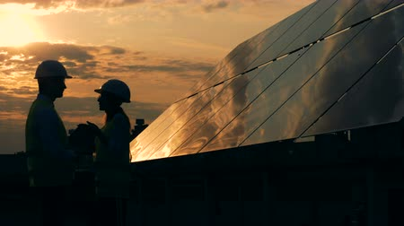 energetyka : Solar panels and two workers silhouettes talking.