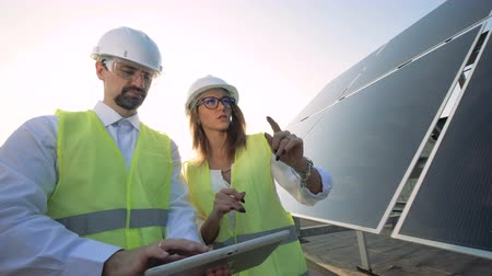 tvořit : A female and a male solar inspectors are having a discussion near a solar module. Green energy concept.