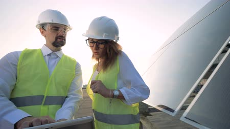 energetyka : Lady engineer is coming to her male colleague and discussing construction project. Solar energy concept.