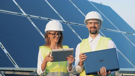 energetyka : A couple of cheerful solar energy inspectors are looking into the camera. Solar energy concept.