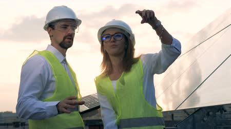 producing energy : A male and a female engineers discussing solar energy standing near solar panels. Solar energy concept.