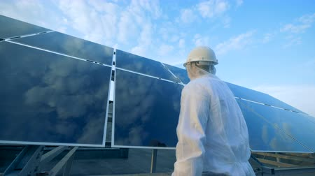 energetyka : Cleaning process of solar arrays reflective surface held by a male worker. Green energy concept.