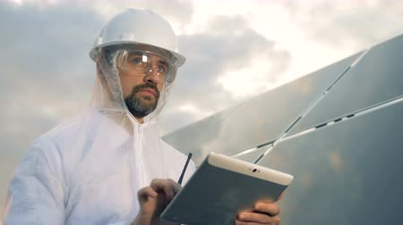 energetyka : Man in protection wear is operating a tablet next to a massive solar installation