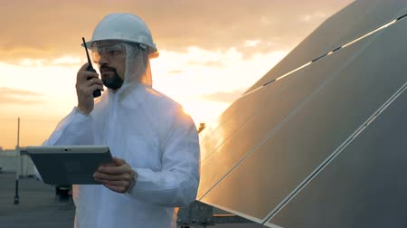 inspector : Sunset landscape on a rooftop with a male expert talking on a transmitter beside a solar battery Stock Footage