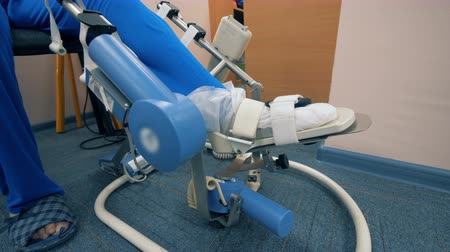 rehabilitasyon : Medical therapy on a leg. Automated machine moves a patients leg in a hospital ward.