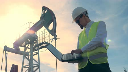 sektör : Sunlit fuel derrick and a male engineer operating a laptop in front of it. Oil industry, petroleum industry, oil sector concept. Stok Video