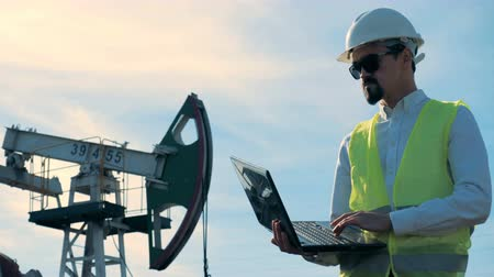 harmful : Working process of a male worker holding a laptop next to a functioning gas derrick. Energy, oil, gas, fuel pumping rig. Stock Footage