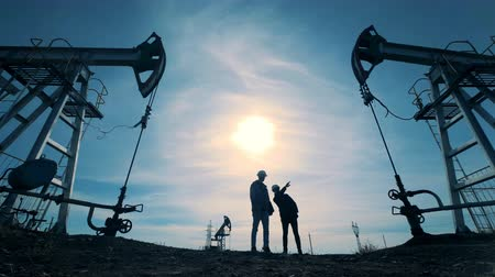 producing energy : Male technicians are shaking hands and walking away from oil-derricks together Stock Footage