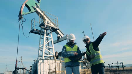 surový : Oil pump with two specialists having a discussion in front of it