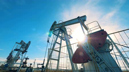 producing energy : Mechanical derricks are pumping oil in sunlight. Oil industry, petroleum industry, oil sector concept. Stock Footage
