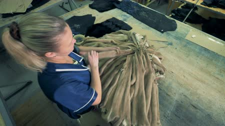 skins : A worker ties animal skins on a table, top view.