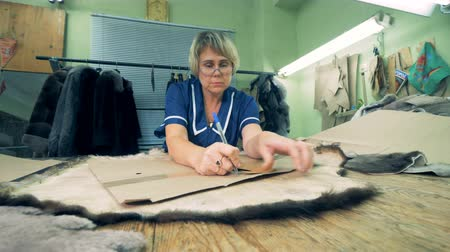 yama işi : A tailor takes measurements of animal skin on a table, close up.