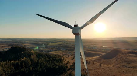 producing energy : The sun and a wind turbine revolving in its background. Wind energy, wind electricity generation concept. Stock Footage