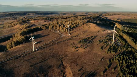 producing energy : Three windmills installed in the open terrain are producing energy. Wind energy, wind electricity generation concept. Stock Footage