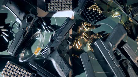калибр : Many black pistols with bullets at a shooting range, top view.