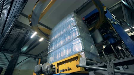 строк : Special machine wraps bottles. Bottle wrapping process at a factory.