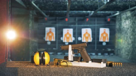 amendment : A gun with headphones and glasses on a table. Ammunition, guns, weapons at a fire range. Stock Footage