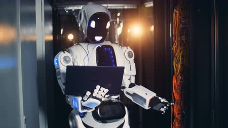 iletmek : A white cyborg types on a laptop in a server room. Robot stands in a room, checking server equipment.