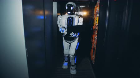 держит : One robot walks in a corridor at a data center, close up.