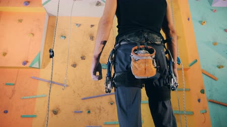 bouldering : A man looks at a climbing wall, close up.