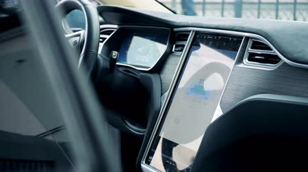 recharging : Interior of an electric car with its recharging process displayed on a panel Stock Footage