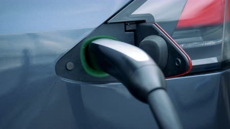recharging : Illuminated socket of an electrocar with a plugged-in nozzle Stock Footage