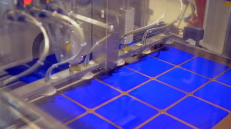 automate : A machine moving small panels in rows, close up.