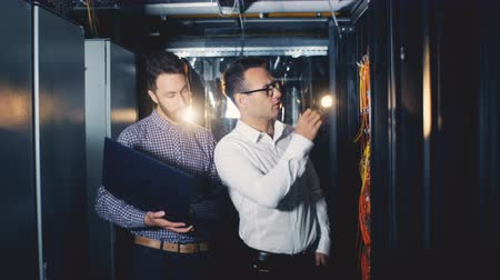 teknisyen : Two workers working in a technology data center.